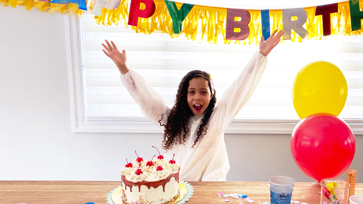 A girl with her hands in the air in back of a table with birthday cake and confetti on it.  A streamer that says happy birthd